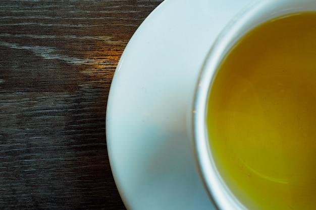Vista recortada parcial de alto ángulo. primer plano de la taza de té sobre fondo de madera vintage