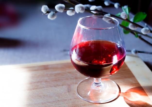 Vista romántica con una copa de vino y una rama de sauce en una tabla de madera.