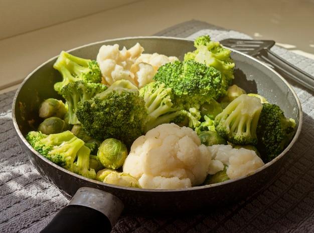 Vista de la sartén con verduras frescas descongeladas y espátula de cocina.