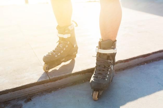 Vista de sección baja de los pies de un hombre con patines en línea