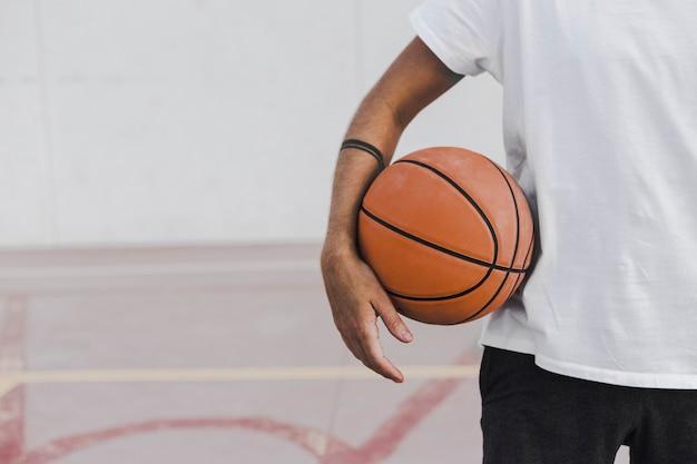 Vista de la sección media de la mano de un hombre con baloncesto.