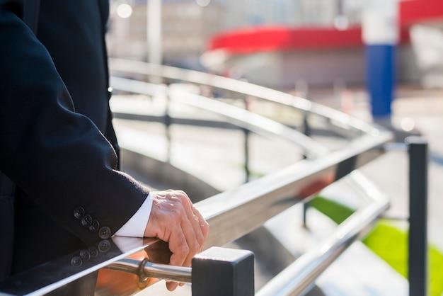 Vista de la sección media de la mano de un hombre de negocios sobre una barandilla.