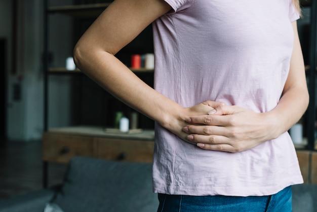 Vista de la sección media de una mujer que sufre de dolor en la cintura. Foto Premium