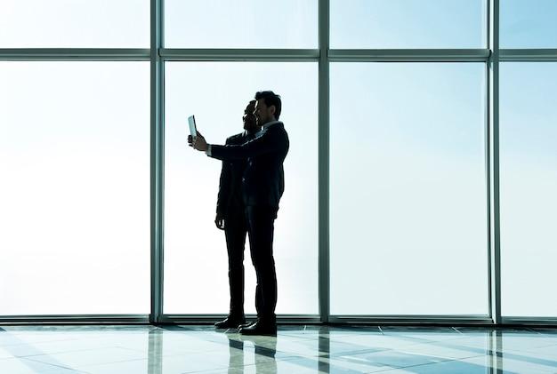 Vista de la silueta de dos hombres de negocios están haciendo fotos selfie.