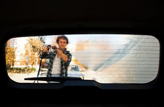Vista de silueta de hombre lavando la ventana de un automóvil