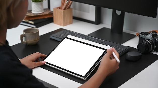 Vista sobre el hombro del diseñador gráfico joven que trabaja con mesa digital en la oficina moderna.