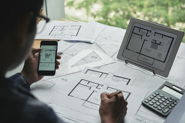 Vista sobre el hombro del diseñador que trabaja con planos
