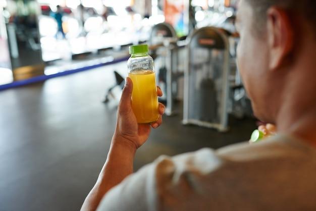 Vista sobre el hombro del hombre irreconocible sosteniendo una botella de jugo de naranja