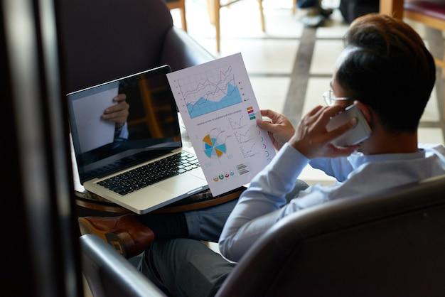Vista sobre el hombro del hombre multitarea revisando documentos financieros y teniendo chat telefónico