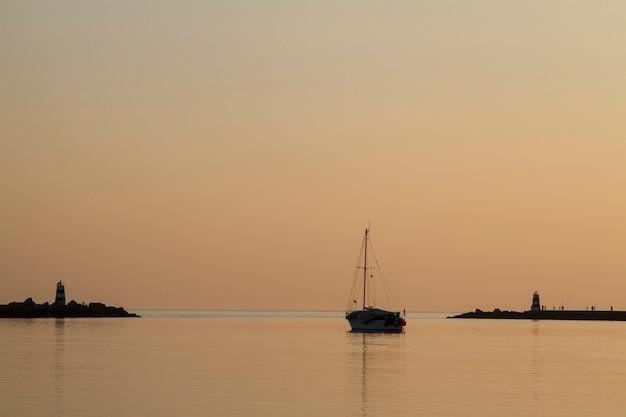 Vista soñadora de los embarcaderos de un rompeolas de la marea en la puesta del sol.