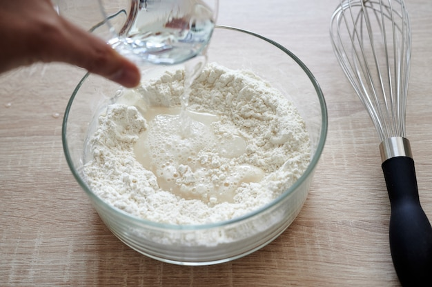 Vista subjetiva de la mano vertiendo agua sobre un recipiente de vidrio con harina, con una chapa agitada al lado