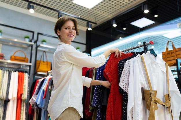 Vista desde el suelo de joven mujer elegir ropa