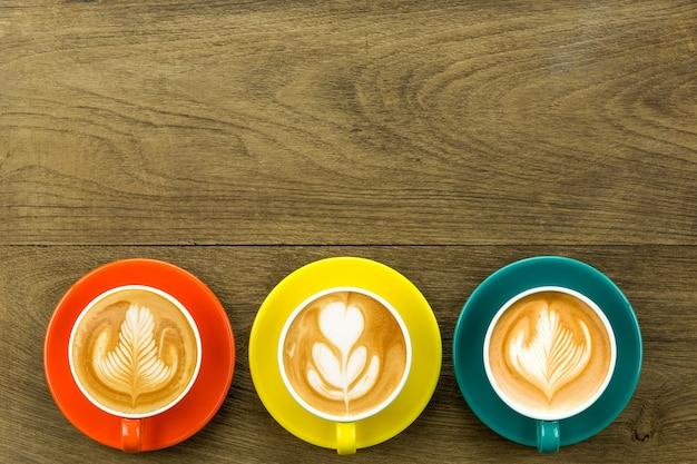 Vista superior de 3 café con leche o café capuchino en taza de color amarillo anaranjado y azul oscuro con arte latte en la mesa de madera.