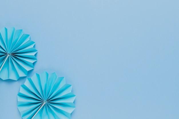 Vista superior del abanico de papel de origami azul sobre fondo liso