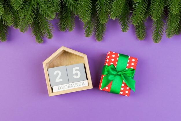 Vista superior del abeto, calendario de madera y caja de regalo en colores.