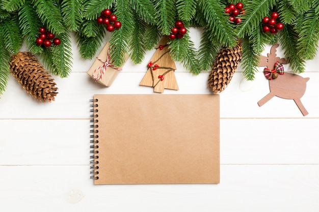 Vista superior de abeto, decoraciones de año nuevo y cuaderno en madera.