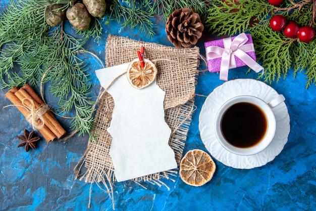 Vista superior abrió cuaderno ramas de abeto conos juguetes de árbol de navidad en superficie azul