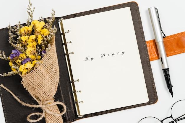 Vista superior de abrir mi libro diario con pluma y flores estáticas sobre fondo blanco