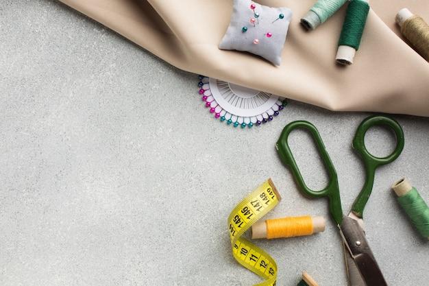 Vista superior de accesorios para coser y tela blanca
