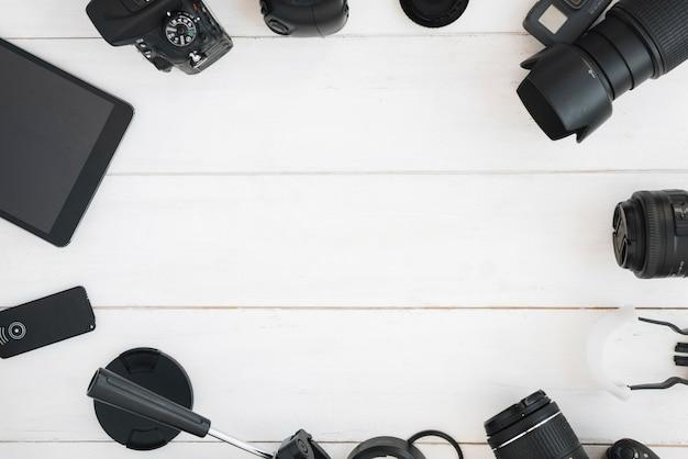 Vista superior de accesorios de fotografía profesional en mesa de madera blanca.