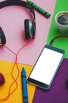 Vista superior de los accesorios de la oficina escritorio. teléfonos inteligentes auriculares en colores de fondo