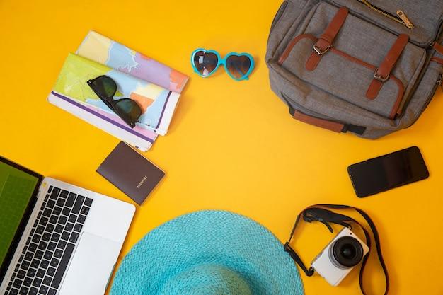 Vista superior de accesorios, pasaporte y laptop del viajero.
