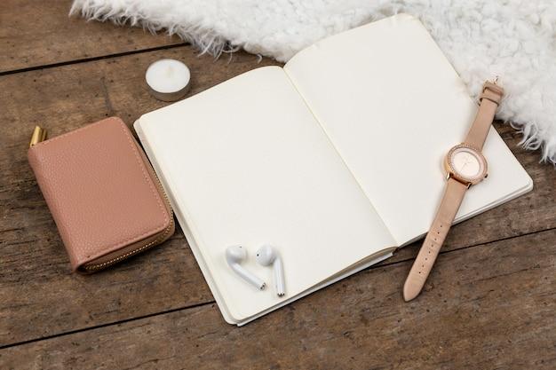 Vista superior de accesorios reloj dorado, bolígrafo, cuaderno, auriculares, tela de piel sobre un fondo de madera.