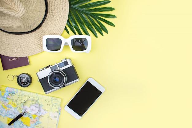 Vista superior de accesorios turísticos con cámaras de cine, mapas, pasteles, sombreros, gafas de sol y teléfonos inteligentes sobre un fondo amarillo.