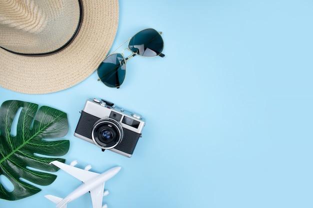 Vista superior de accesorios turísticos con cámaras de cine, sombreros, gafas de sol, teléfonos inteligentes y hojas de verano sobre un fondo azul.