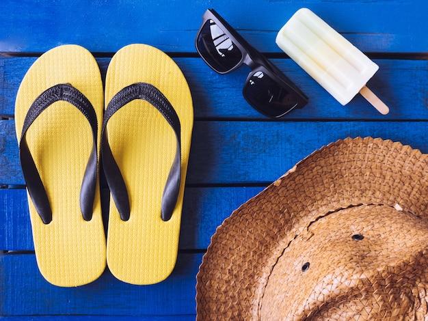 Vista superior de accesorios de verano en el piso de madera azul.