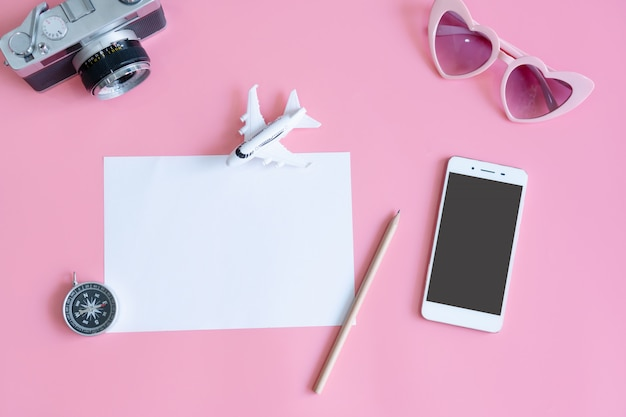 Vista superior de accesorios de viaje y documento sobre tabla de color rosa, concepto de viaje. lay flat, espacio de copia