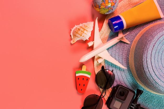 Vista superior de accesorios de viajero, hoja de palma tropical y avión en rosa