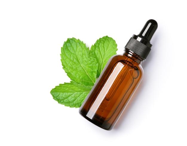 Vista superior de aceite esencial de menta en frasco gotero ámbar con hojas de menta fresca aisladas sobre fondo blanco.