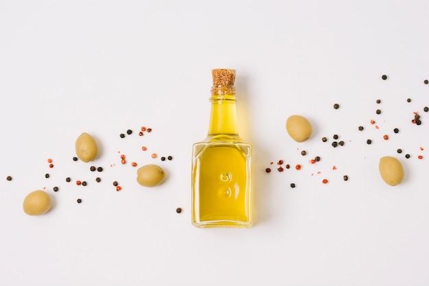 Vista superior de aceite de oliva con aceitunas y especias