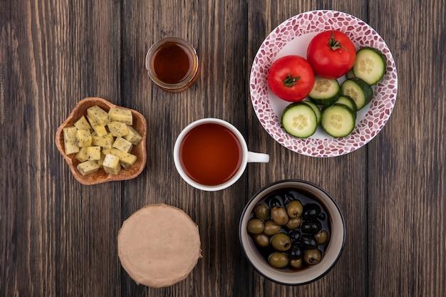 Vista superior de aceitunas frescas en un recipiente con una taza de té con verduras con rodajas de queso picadas sobre un fondo de madera