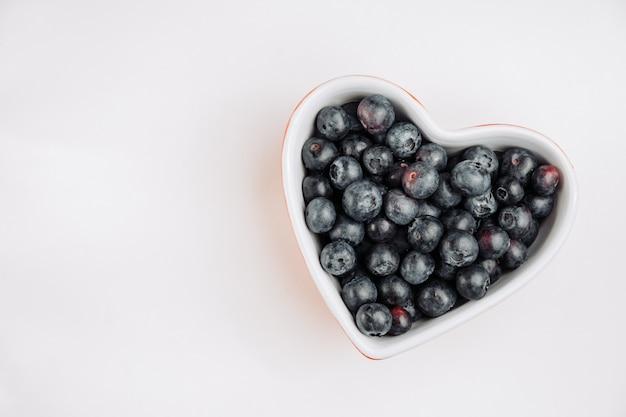 Vista superior aceitunas negras en un recipiente en forma de corazón sobre fondo blanco. espacio horizontal para texto