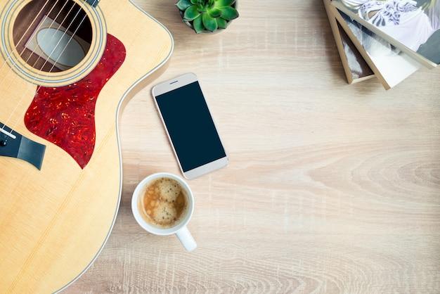 Vista superior de la acogedora escena del hogar. libros, mantas de lana, taza de café, teléfono y plantas suculentas sobre madera. copia espacio, maqueta.