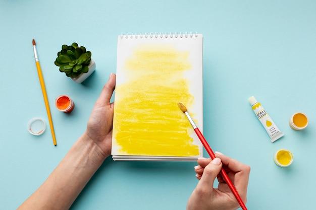 Vista superior de la acuarela amarilla en el cuaderno