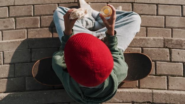 Vista superior del adolescente con patineta comiendo un sándwich y bebiendo jugo