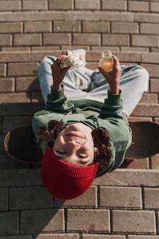 Vista superior del adolescente sonriente con patineta comiendo un sándwich y bebiendo jugo