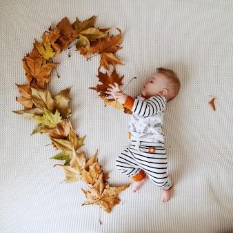 Vista superior del adorable bebé en ropa de bebé lindo acostado en la cama y haciendo forma de corazón con hojas de otoño.