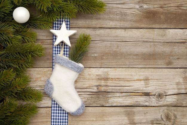 Vista superior de adornos navideños y un calcetín en una mesa de madera con ramas de árboles