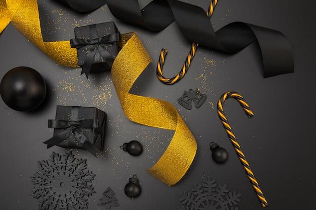Vista superior de adornos navideños con cinta dorada y regalos.