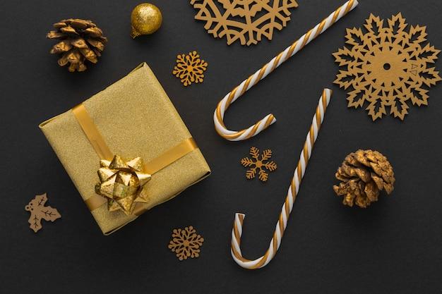 Vista superior de adornos navideños dorados y presente.