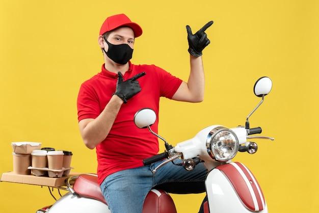 Vista superior del adulto joven con blusa roja y guantes de sombrero en máscara médica entregando orden sentado en scooter apuntando hacia arriba sobre fondo amarillo