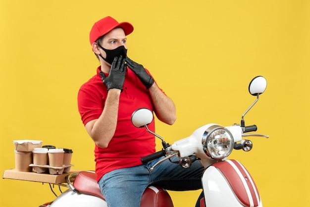 Vista superior del adulto joven con blusa roja y guantes de sombrero en máscara médica entregando orden sentado en scooter centrado en algo sobre fondo amarillo