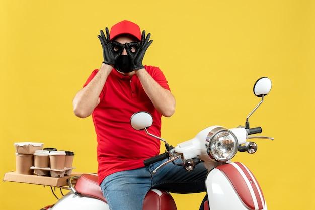 Vista superior del adulto joven con blusa roja y guantes de sombrero en máscara médica entregando orden sentado en scooter haciendo gesto de anteojos sobre fondo amarillo