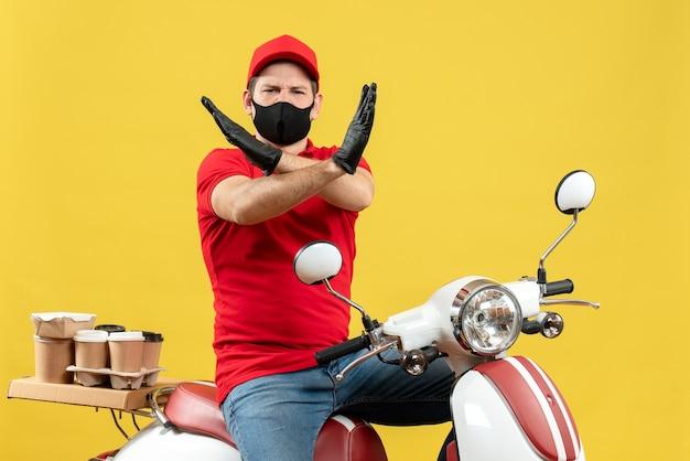 Vista superior del adulto joven con blusa roja y guantes de sombrero en máscara médica entregando orden sentado en scooter haciendo gesto de parada sobre fondo amarillo