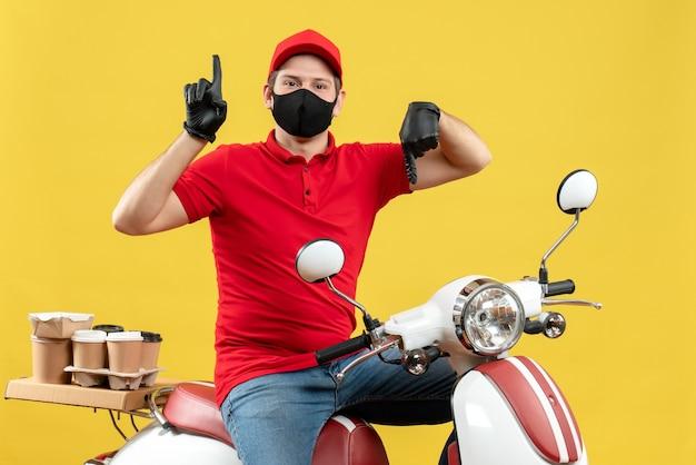 Vista superior del adulto joven con blusa roja y guantes de sombrero en máscara médica entregando orden sentado en scooter con los pulgares hacia arriba y hacia abajo sobre fondo amarillo