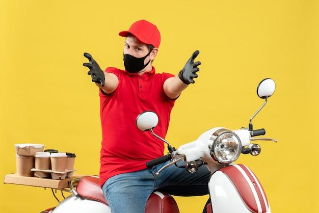 Vista superior del adulto joven con blusa roja y guantes de sombrero en máscara médica entregando orden sentado en scooter sintiéndose confundido extendiendo sus brazos hacia adelante sobre fondo amarillo